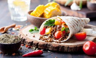 Vegan tortilla wrap, roll with grilled vegetabes and lentil and boiled corn cob on a wooden background